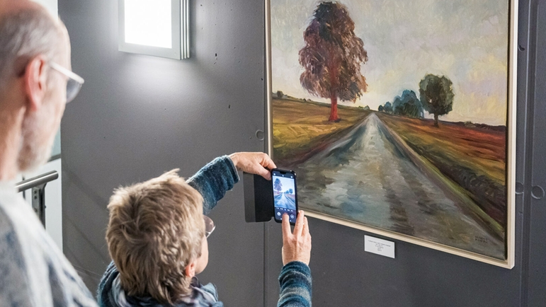 Visitors of the vernissage marvel at the works of art by painter Magdalena Willems-Pisarek
